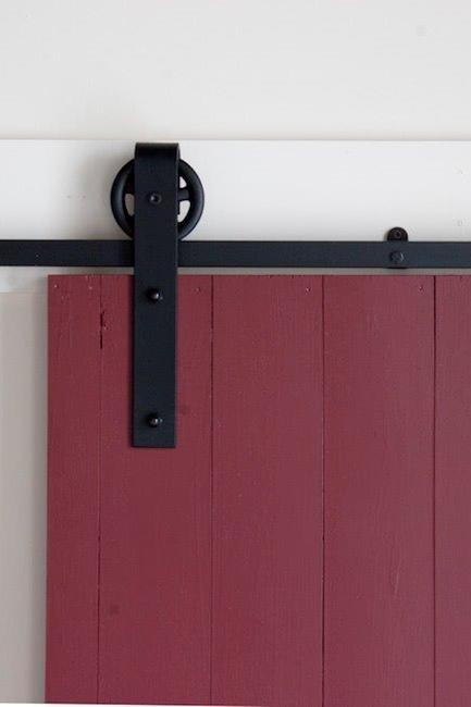 Photo of our large spoked flat track hardware mounted on a red barn door. Hardware kit manufactured by Better Barns, sold by Specialty Doors