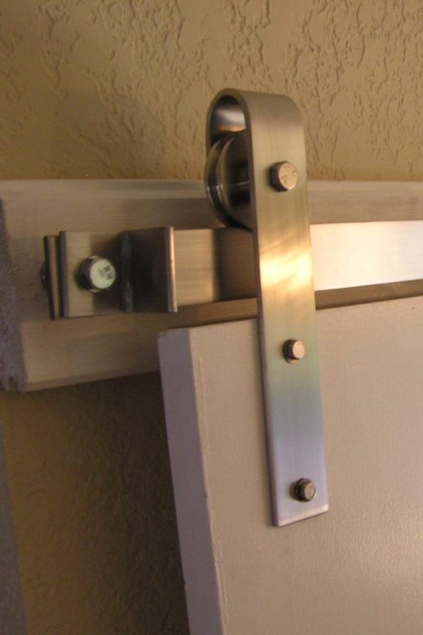 Product photo of a stainless steel 430 flat track hardware kit installed on a white door.